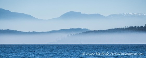 Blue sea and skies with layers of fog and boats in distance