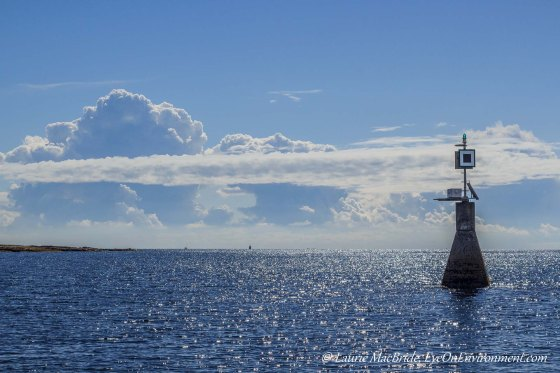 Navigational light with bright sun on water and clouds